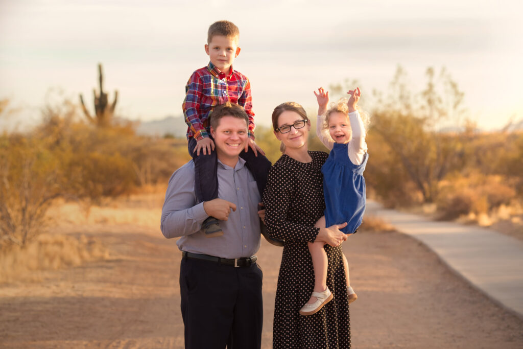 Posed but Candid family photo of family of four in a desert hiking trail in Phoenix Arizona